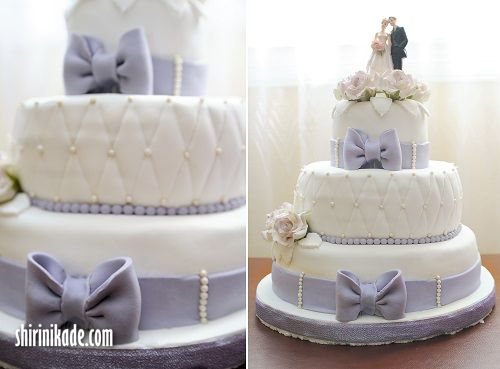 Wedding cake with purple bow on light background